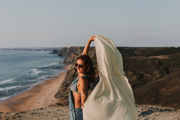 Portret pięknej szczęśliwej młodej kobiety gry z chusteczką i wiatrem na szczycie wzgórza. czas letni styl życia