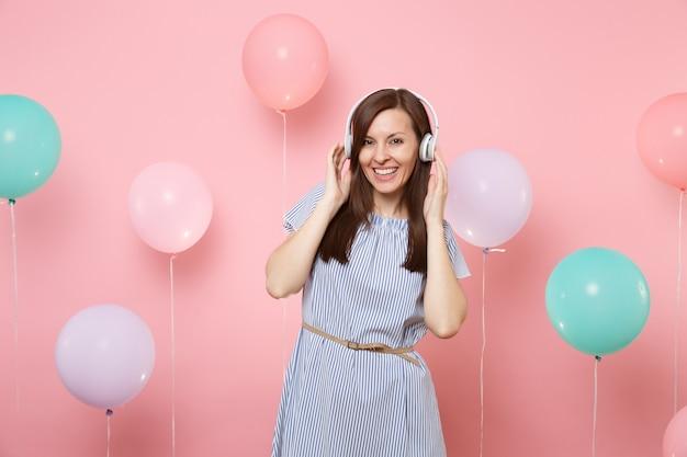 Portret pięknej szczęśliwej młodej kobiety ze słuchawkami na sobie niebieską sukienkę słuchania muzyki, trzymając ręce w pobliżu głowy na pastelowym różowym tle z kolorowymi balonami. koncepcja strony urodziny wakacje.