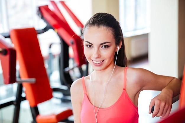 Portret Pięknej Szczęśliwej Młodej Sportsmenki W Słuchawkach Do Słuchania Muzyki W Siłowni Premium Zdjęcia