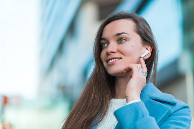 Portret pięknej szczęśliwej radosnej brunetki biznesowa kobieta z bezprzewodowymi białymi hełmofonami w mieście. współczesny styl życia i technologia