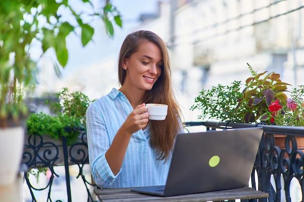 Portret pięknej szczęśliwej ślicznej radosnej uśmiechniętej romantycznej freelancerki z filiżanką aromatycznej kawy w dłoniach i laptopem do zdalnej internetowej przytulnej pracy na balkonie