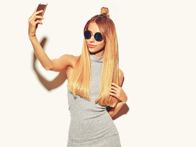 Portret pięknej szczęśliwej ślicznej uśmiechniętej blondynki kobiety w przypadkowych szarych modnisiów letnich ubraniach bez makeup odizolowywających na bielu bierze selfie
