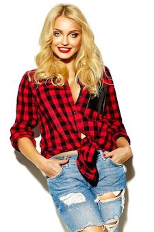 Portret pięknej szczęśliwej ślicznej uśmiechniętej blondynki kobiety zła dziewczyna w przypadkowej czerwonej modniś letniej flanelowej koszula w kratkę i niebieskich dżinsach odziewa z czerwonymi wargami