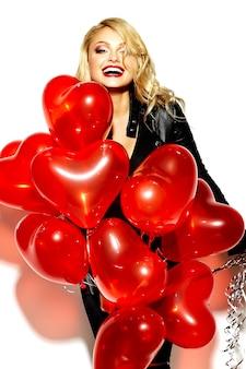 Portret pięknej szczęśliwej słodkiej uśmiechniętej blondynki kobiety dziewczyny mienia w jej rękach czerwonych serc balony w przypadkowych czarnych modnisiów ubraniach