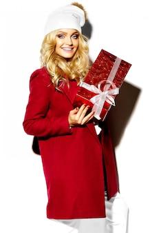 Portret pięknej szczęśliwej słodkiej uśmiechniętej blondynki kobiety dziewczyny mienia w jej rękach duży bożenarodzeniowego prezenta pudełko w przypadkowej czerwonej modniś zimy ubraniach