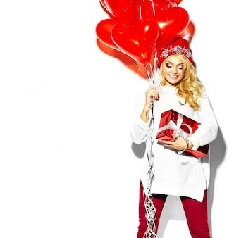 Portret pięknej szczęśliwej słodkiej uśmiechniętej blondynki kobiety dziewczyny trzymającej w rękach duże pudełko na prezenty świąteczne i balony serca w dorywczo czerwonych ubraniach zimowych hipster, w białym ciepłym swetrze