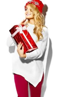 Portret pięknej szczęśliwej słodkiej uśmiechniętej kobiety blondynka trzyma w dłoniach duże pudełko na prezent świąteczny w swobodnych czerwonych ubraniach zimowych hipster, w białym ciepłym swetrze
