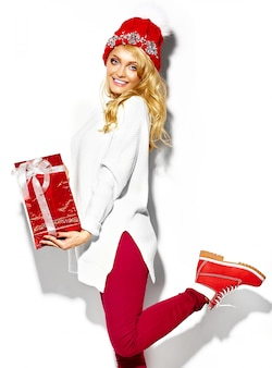 Portret pięknej szczęśliwej słodkiej uśmiechniętej kobiety blondynka trzyma w dłoniach duże świąteczne pudełko w przypadkowych czerwonych ubraniach zimowych hipster, w białym ciepłym swetrze stojącym na jednej nodze