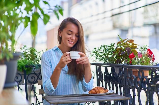 Portret pięknej, szczęśliwej uroczej, radosnej, uśmiechniętej romantycznej kobiety z filiżanką aromatycznej kawy w dłoniach i talerzem świeżo upieczonego rogalika na stole rano na balkonie