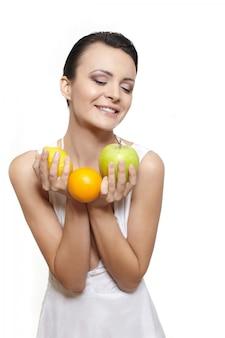 Portret pięknej szczęśliwej uśmiechnięte dziewczyny z owocami cytryny i zielone jabłko i pomarańcza na białym