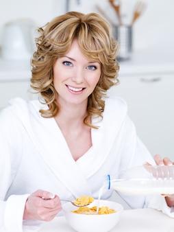 Portret pięknej szczęśliwej uśmiechniętej kobiety jedzenie płatków kukurydzianych w kuchni