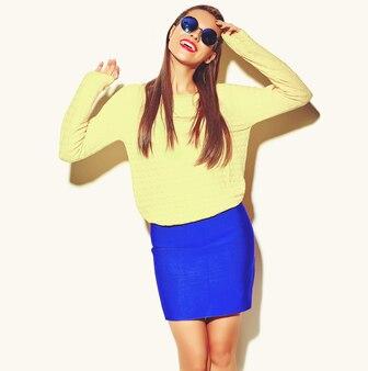 Portret pięknej szczęśliwy ładny uśmiechnięty brunetka dama dziewczynka w dorywczo kolorowe hipster żółte letnie ubrania z czerwonymi ustami na białym tle