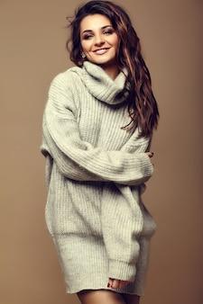 Portret pięknej szczęśliwy słodki ładny uśmiechnięta brunetka dama dziewczyna w dorywczo hipster ciepły szary sweter ubrania