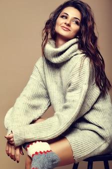 Portret pięknej szczęśliwy słodki ładny uśmiechnięty brunetka dama dziewczynka w dorywczo hipster ciepły szary sweter ubrania, siedząc