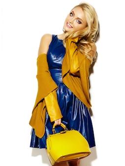 Portret pięknej szczęśliwy słodki uśmiechający się kobiety blondynka w dorywczo hipster ciepłe zimowe ubrania sweter, z żółtą torebką