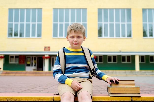 Portret pięknej szkoły chłopiec szuka bardzo szczęśliwy na zewnątrz w czasie dnia.