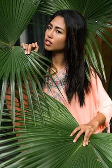 Portret pięknej tajskiej kobiety nad tropikalnymi liśćmi. koncepcja spa i relaksu. etniczny styl boho.
