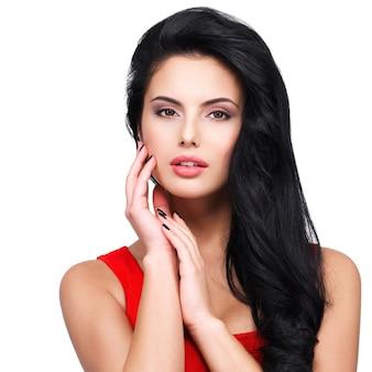 Portret pięknej twarzy młodej kobiety z długimi brązowymi włosami w czerwonej sukience