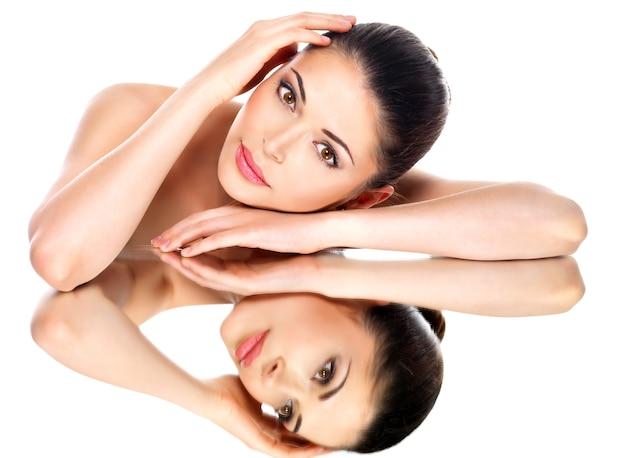 Portret pięknej twarzy młodej ładnej kobiety z odbiciami zdrowej skóry w lustrze
