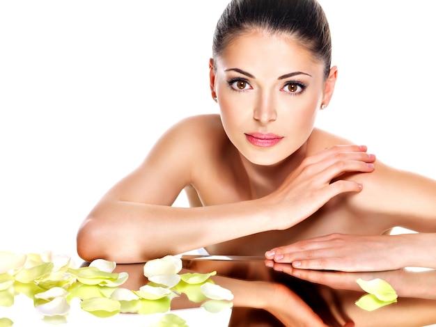 Portret pięknej twarzy młodej ładnej kobiety ze zdrową skórą i różowe kwiaty odbicia w lustrze