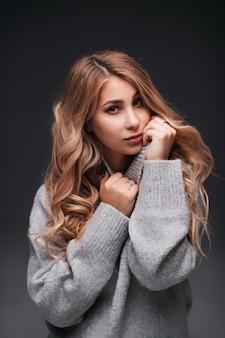 Portret pięknej uroczej kobiety w swobodnym szarym swetrze na czarnej ścianie