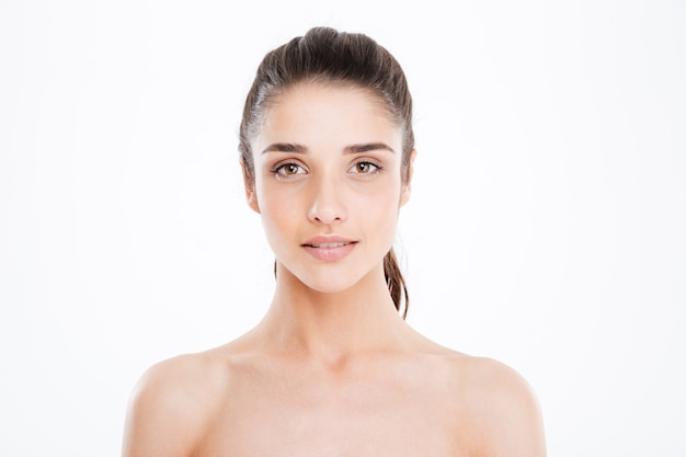 Portret pięknej, uroczej młodej kobiety z idealną skórą na białej ścianie