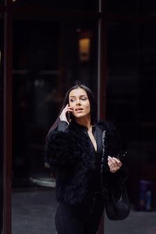 Portret pięknej uśmiechnięta dziewczyna z długimi ciemnymi włosami na sobie czarny. młoda kobieta przy użyciu telefonu komórkowego