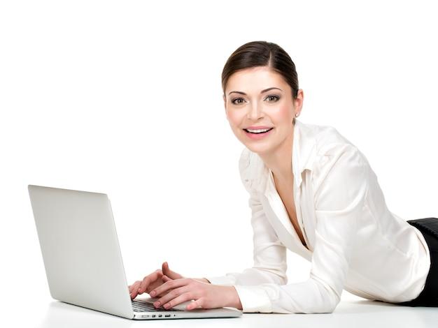 Portret pięknej uśmiechnięta kobieta z laptopem w białej koszuli na podłodze - na białym tle.