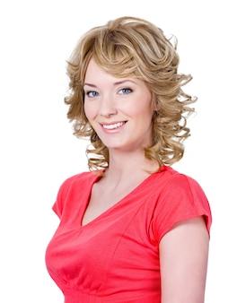 Portret pięknej uśmiechnięta młoda kobieta w czerwieni z kręconymi blond włosami