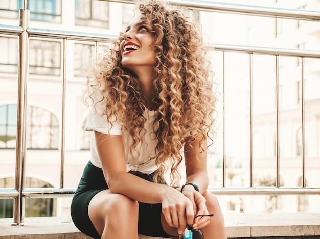 Portret pięknej uśmiechnięta modelka z fryzurą afro loki ubrana w letnie ubrania hipster. seksowna beztroska dziewczyna siedzi na tle ulicy. modna, zabawna i pozytywna kobieta dobrze się bawi