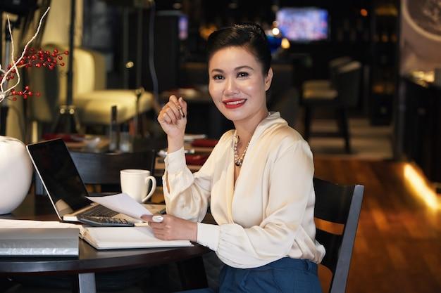 Portret pięknej uśmiechniętej bizneswoman pracującej przy stole w restauracji i podpisującej dokumenty