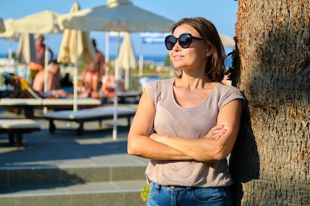Portret pięknej uśmiechniętej dojrzałej kobiety relaksującej się w hotelu, kobieta w okularach przeciwsłonecznych stojąca w pobliżu palmy z założonymi rękoma, kopia przestrzeń. wakacje, lato, turystyka, kurort, ludzie w średnim wieku