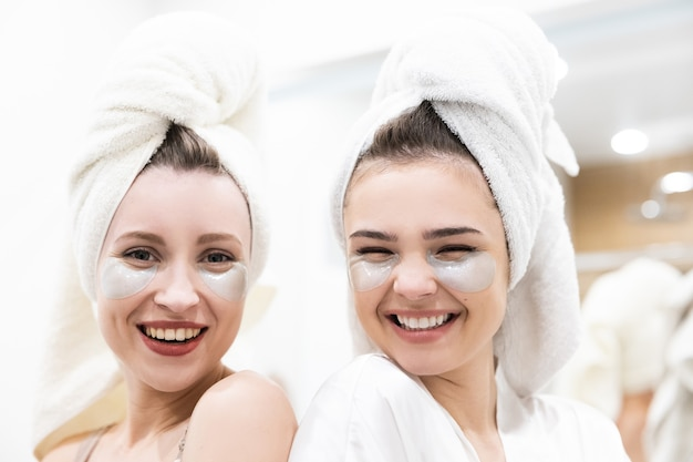 Portret pięknej uśmiechniętej dziewczyny europejskiej. młode kobiety z przepaską pod oczami na twarzy i owiniętymi ręcznikami kąpielowymi na głowach. koncepcja strony dziewcząt. rozmyj wnętrze łazienki w nowoczesnym mieszkaniu