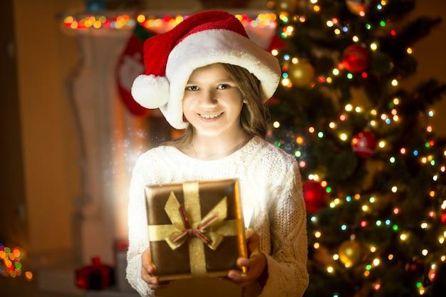 Portret pięknej uśmiechniętej dziewczyny pozującej z błyszczącym pudełkiem na choinkę