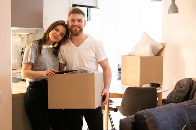 Portret pięknej uśmiechniętej europejskiej pary trzymającej karton z rzeczami w domu. koncepcja przeprowadzki do nowego mieszkania. idea młodej rodziny. wnętrze apartamentu typu studio. słoneczny dzień