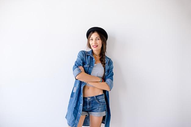 Portret pięknej uśmiechniętej hipster dziewczyny w dżinsach,