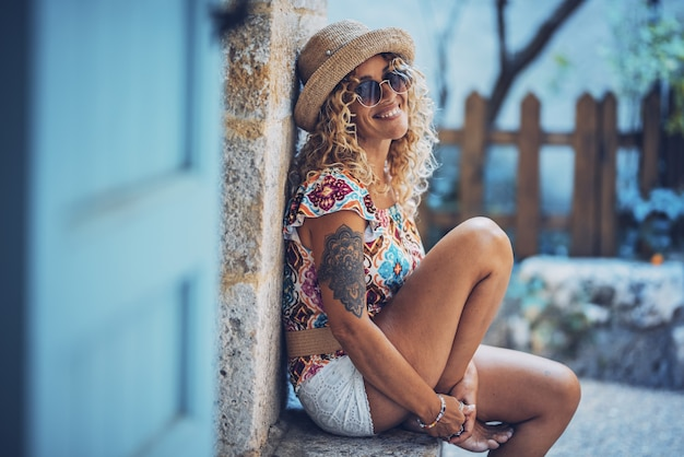 Portret pięknej uśmiechniętej hipster młodej kobiety w okularach przeciwsłonecznych i słomkowym kapeluszu siedzi na zewnątrz. stylowa wytatuowana kobieta w dobrym nastroju spędzająca wolny czas relaksując się na świeżym powietrzu