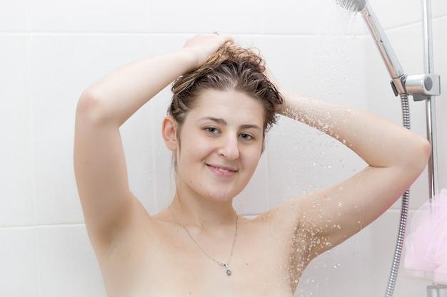 Portret pięknej uśmiechniętej kobiety myjącej włosy pod prysznicem