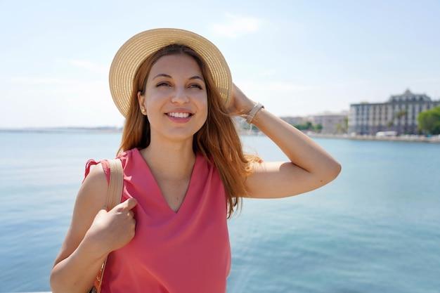 Portret pięknej uśmiechniętej kobiety patrzącej z boku na morze w mieście