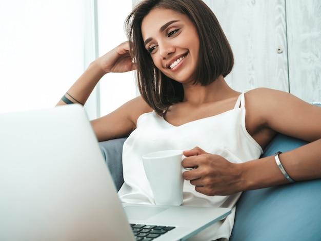 Portret pięknej uśmiechniętej kobiety ubranej w białą piżamę. beztroski model siedzący na krześle z miękkiej torby i korzystający z laptopa.