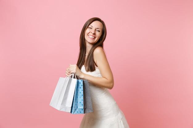 Portret pięknej uśmiechniętej kobiety w białej sukni trzymającej wielokolorowe torby z zakupami po zakupach