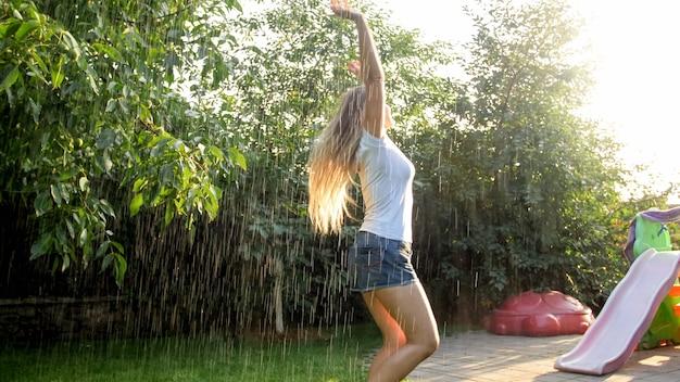 Portret pięknej uśmiechniętej kobiety w mokrych ubraniach, ciesząc się ciepłym deszczem w ogrodzie przydomowym domu o zachodzie słońca. dziewczyna bawi się i bawi na świeżym powietrzu w lecie
