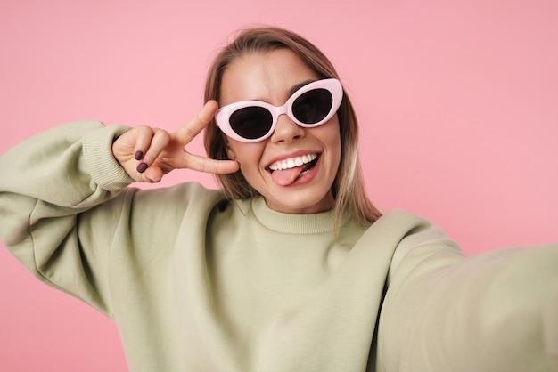 Portret pięknej uśmiechniętej kobiety w okularach przeciwsłonecznych gestykulującej znak pokoju i biorącej selfie na różowym tle