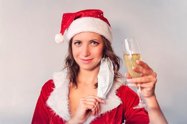 Portret pięknej uśmiechniętej kobiety w świątecznym kapeluszu i sukience trzymającej kieliszek do szampana, stojąc na szarym tle. kobieta zdjęła maskę ochronną przed wirusem, koniec kwarantanny.