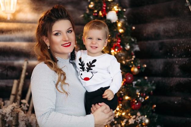 Portret pięknej uśmiechniętej kobiety z fryzurą i makijażem, trzymając jej cudowne dziecko przed zdobioną choinką
