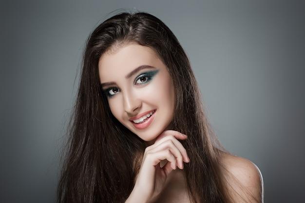 Portret pięknej uśmiechniętej kobiety z zielonym wieczorowym makijażem na ciemnym tle
