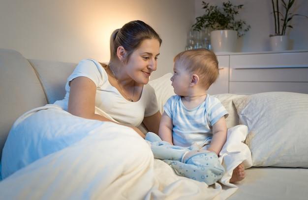 Portret pięknej uśmiechniętej matki leżącej na łóżku z dzieckiem przed pójściem spać