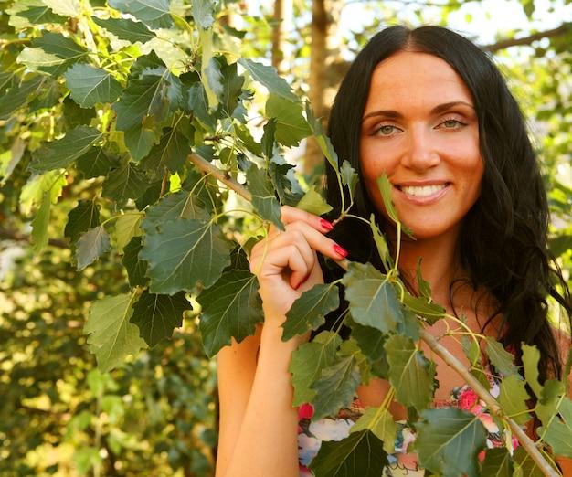 Portret pięknej, uśmiechniętej młodej kobiety na zewnątrz pod zielonymi liśćmi.