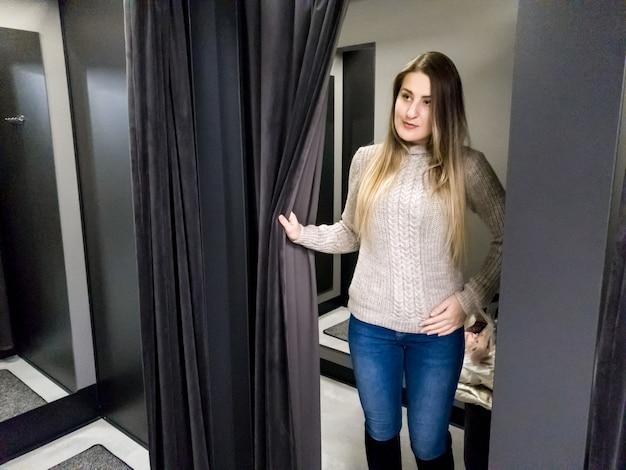 Portret pięknej uśmiechniętej młodej kobiety przymierza ciepły wełniany sweter w szatni centrum handlowego