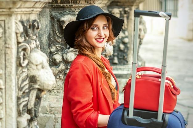 Portret pięknej uśmiechniętej młodej kobiety rasy kaukaskiej w czarnym kapeluszu z bagażem, siedzącej w starożytnym budynku, patrzącej na kamerę na zewnątrz